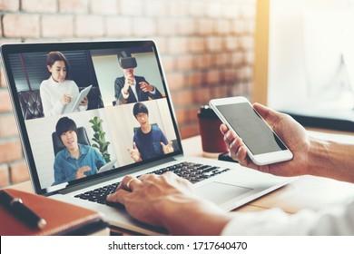 Asiatischer Hobbyarbeitnehmer nutzt intelligente Arbeits- und Videokonferenzen mit asiatischem Team und nutzt Laptop und Tablet online in Video-Call für neue Projekte