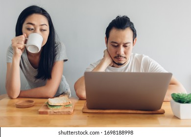 Asian man is working online with his wife support in concept of work from home.