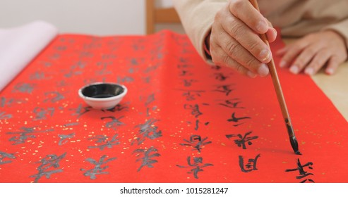 Asian man writing chinese calligraphy on red paper