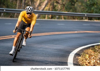 Asian man in yellow cycling jersey riding on road bike with willful face.