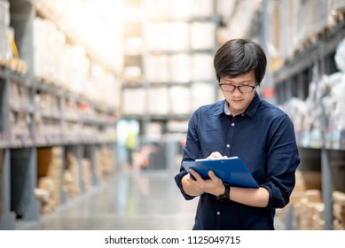 Asian manager man doing stocktaking of products in cardboard box on shelves in warehouse by using clipboard and pen. Male professional assistant checking stock in factory. Physical inventory count.