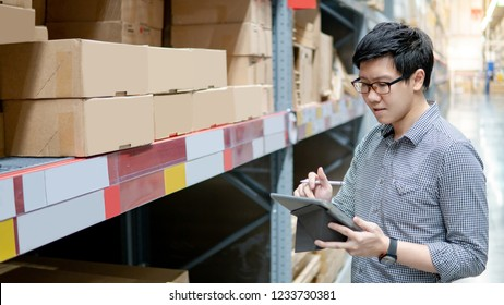 Asian manager man doing stocktaking of products in cardboard box on shelves in warehouse using digital tablet and pen. Male professional assistant checking stock in factory. Physical inventory count.