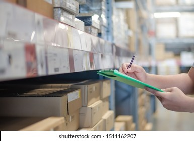 Asian manager man doing stocktaking of products management in cardboard box on shelves in warehouse using clipboard file and pen. Male professional assistant checking stock in factory.