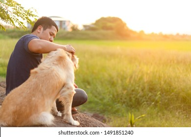 Asian man's sitting at ground with his golden retriever for seeing a sunset.