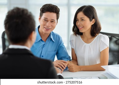 Asian married couple at the meeting with real estate agent