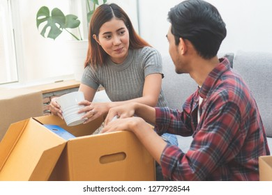 Asian married couple start new family life concept. Woman and man unpacking messy boxes after moving in new house together.