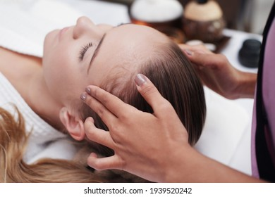 Asian Massage therapist woman is making traditional head and facial treatment massage to Caucasian female is laying on bed at alternative medicine healing spa Center in Thailand.