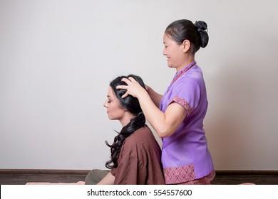 Asian masseur doing thai head massage for caucasian woman in spa salon