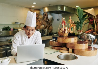 Asian mature chef in uniform searching for online recipe in his laptop computer while standing in the kitchen