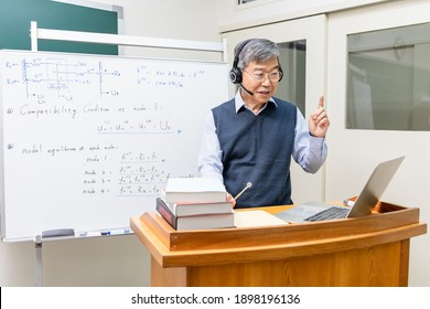 Asian mature male professor wearing headset is teaching Engineering online through laptop in classroom at graduate school
