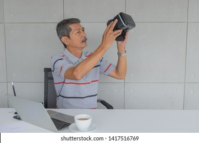 Asian Mature man, Holding VR glasses for testing new modern technology. front on the desk. there are white coffee mug and laptop computer, pen in the office room.