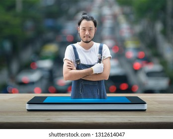 Asian mechanic car engine in uniform with tools on modern smart mobile phone screen on wooden table over blur of rush hour with cars and road in city, Business repair car service online concept
