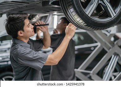 Asian mechanic Checking and torch tire in maintainance service center which is a part of showroom, technician or professional work for customer concept