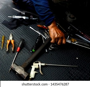 An Asian mechanic is firmly holding a tool with his right hand. His automotive tools are randomly displayed; sledgehammer, screwdrivers, wrenches, pliers,bradawl. Main focus : his hand & wrenches.