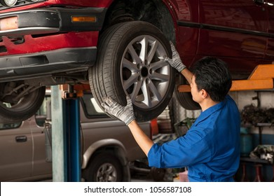 Asian mechanic is looking at the tire to checking and assembles the wheel