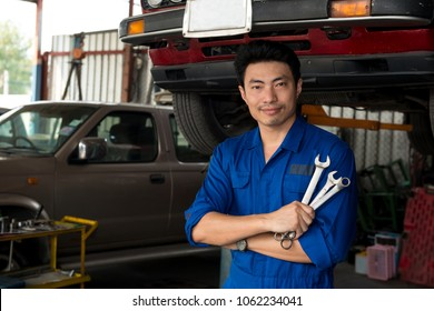 Asian mechanic looking under the car pose looks at camera and hold tools in hand, japanese mechanic portrait style, mechanic maintenance working under car
