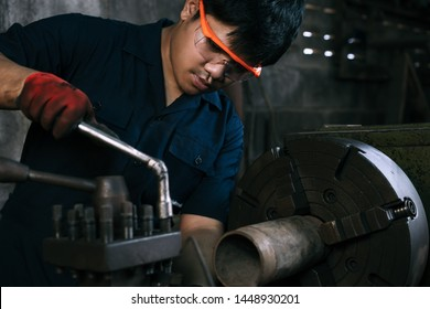 Asian mechanical engineer operating industrial lathe machine - Millennial internship boy training on manufacturing fabrication equipment - Diverse skilled hispanic immigrant factory worker in workshop