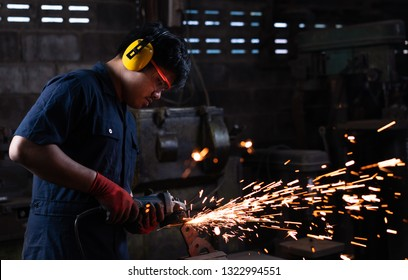 Asian mechanical engineer worker wearing safety equipment and operating angle grinder - Metal factory employee working with power tools in dark industrial workshop with flash sparks - Industry concept