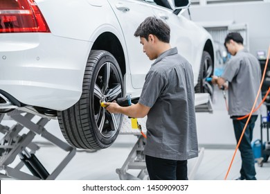 Asian mechanics checking the car wheels at maintainance service center for in showroom