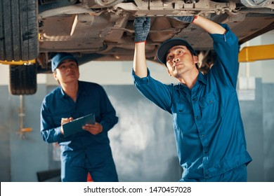 Asian mechanics in uniform inspecting suspended vehicle in garage and taking notes in documents