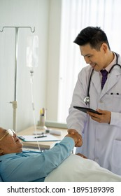 Asian medical doctor with stethoscope caring senior old patient on bed in hospital