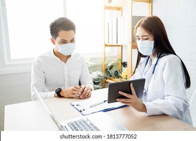 Asiatische Klinik für medizinische Versorgung Arzt, der die Diagnose männlicher Patientin mit Tablette mit chirurgischer Maske Schutzinfektion Infektionskrankheit untersucht, und der zu Hause moderne Bürotechnologie-Laptop arbeitet