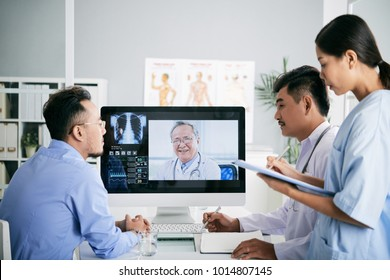 Asian medical interns consullting with doctor online