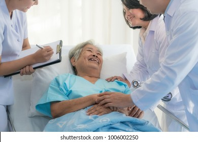 Asian medical team of doctors examining and talking to ASian elderly woman patient, health care people take note on clipboard in hospital.