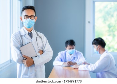 Asian medical team wearing medical masks technology network team meeting concept. Doctor at a table discussing a patients records working, Online medical treatment, New normal