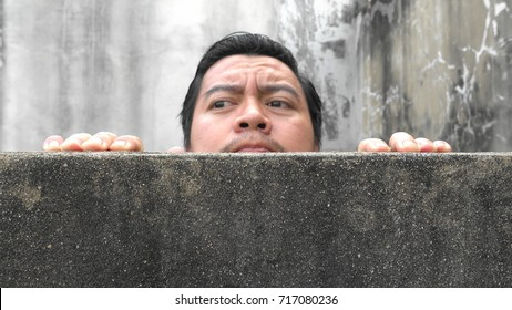Asian men climb up concrete walls appearing suspiciously