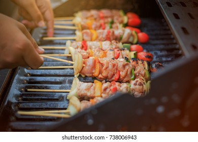 Asian men are cooking for a group of family to eat barbecue (BBQ) grill for family enjoying christmas and New Year.