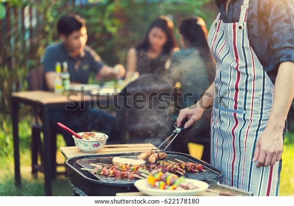Asiatische Männer kochen für eine Gruppe von Freunden Grill
