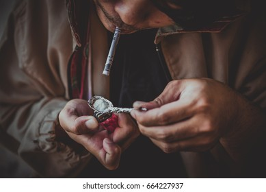 Asian men are drug addicts to inject heroin into their veins themselves.world anti drug day concept,dark tone