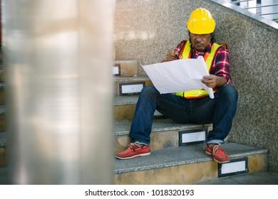 Asian men engineer working on blueprint.