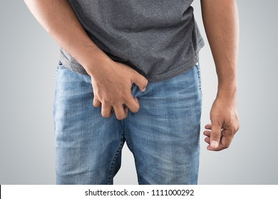 Asian men grab or cover his crotch against gray background. Epididymo-orchitis. The concept of male health problems.