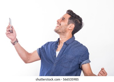 Asian men looking to the sky  vibrating with excitement and happiness, holding  a cellphone on the right  hand