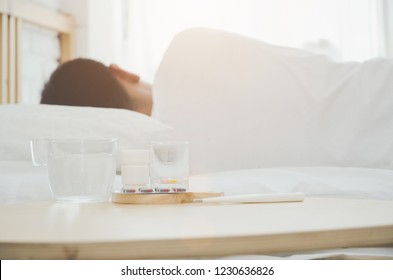 Asian men sick Lie on the white bed in the room in the morning.In the bedroom there was a man sleeping in it.Warm tone.Do not focus on objects.
