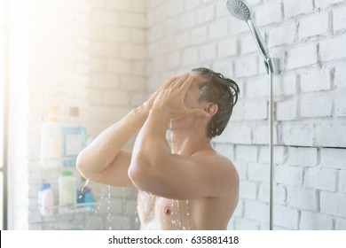 Asian men are taking a shower in the bathroom, he is happy and relaxed.
