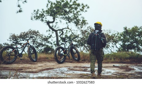 Asian men travel photograph nature. Travel relax ride a bike Wilderness in the wild.Stand on the line. In the meadow in the woods. Thailand