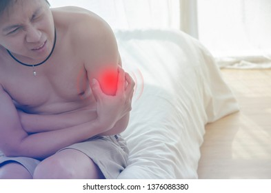 Asian men with upper arm pain.In the white bedroom there are boy. Guys are squeezing the upper arm.The main subject of this image is not in focus.