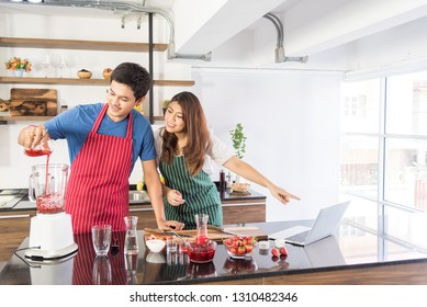Asian men wearing red aprons is pouring strawberrie syrup in the blender and his girlfriend point to the notbook how to do strawberrie smoothie in the kitchen.