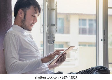 Asian men in white t-shirts are using the tablet to work on vacations.