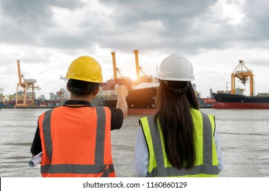 Asian men and women engineers working in Shipping Containers port