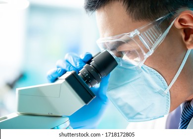 asian microbiologist biotechnology researcher or medical worker look microscope in the lab