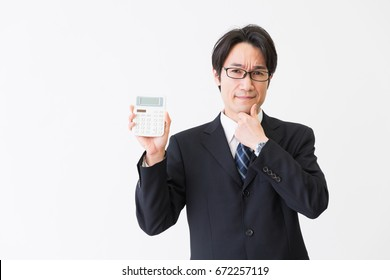 Asian middle age asian businessman having an electronic calculator,think,