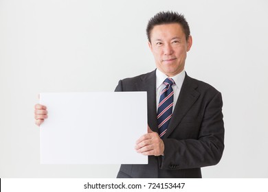 Asian middle age businessman holding blank white board,
