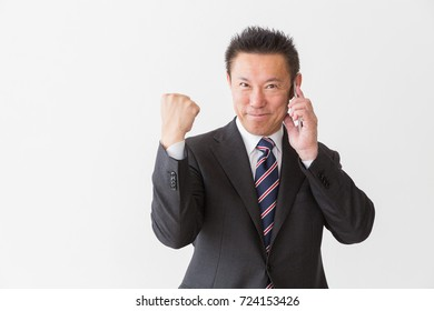Asian middle age businessman who talks on the telephone