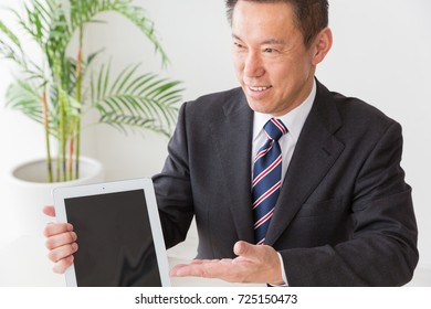 Asian middle age businessman who uses  tablet computer,customers