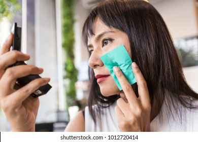 Asian middle age using green oil clear sheet which Oil absorbing blotting sheets to remove excess oil on oily face