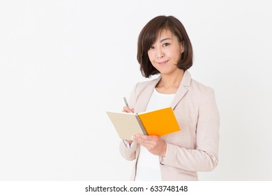 Asian middle age woman filling out a notebook